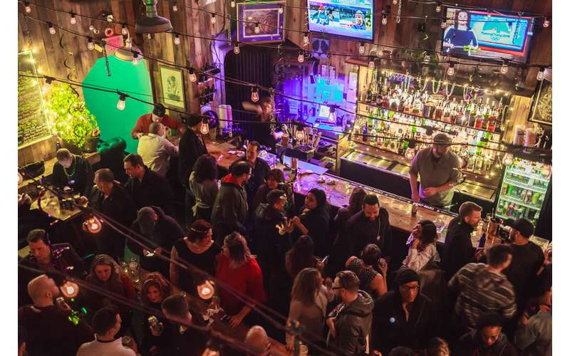 overhead view of crowd of people hanging out inside a bar area