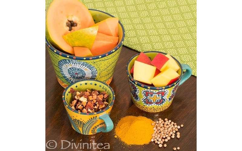 orange fruits near tea leaves
