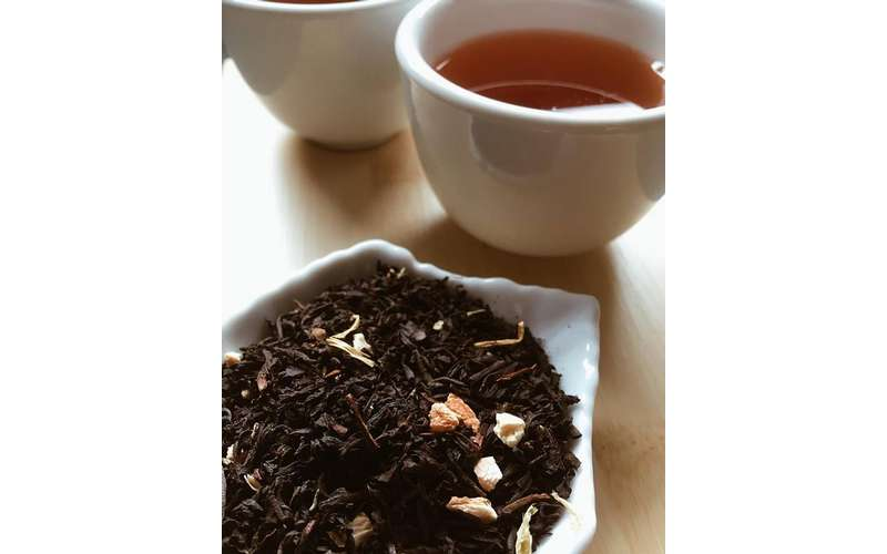 a cup of brown tea near tea leaves