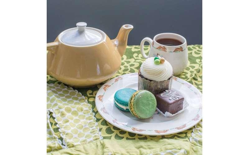 a teapot near a mug and plate of treats
