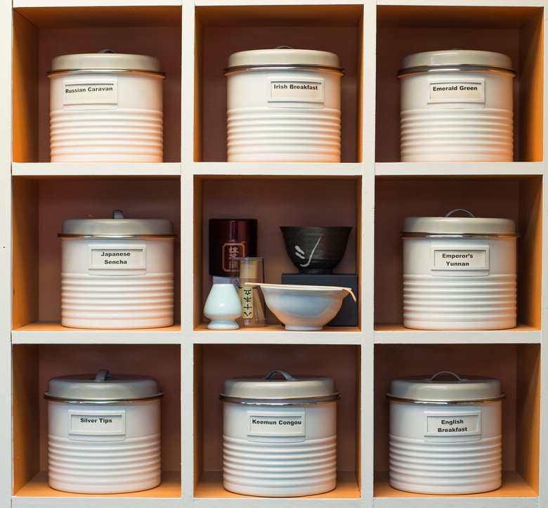 nine shelves, eight of which are filled with tea cannisters and the ninth of which has other tea-related products