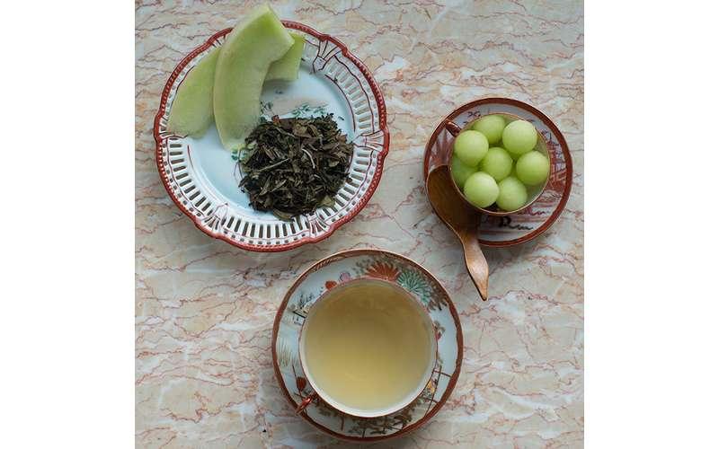 white tea in a cup near green melon
