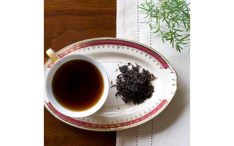 a dark cup of tea on a plate near tea leaves