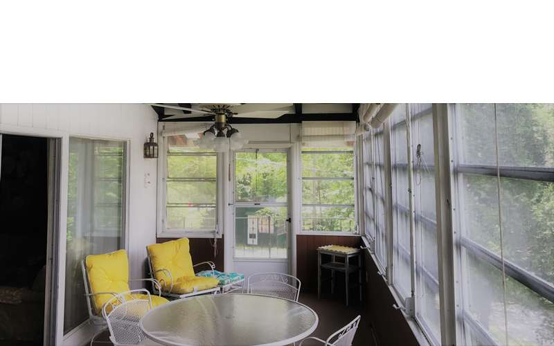 an enclosed porch with a table