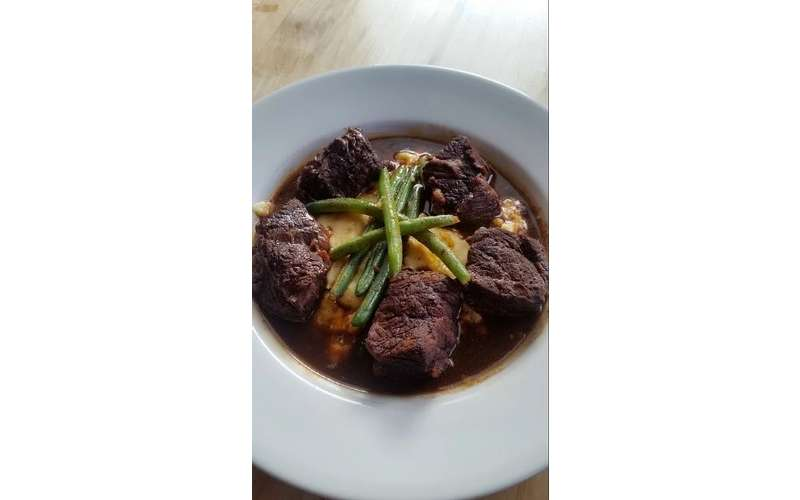 round plate of meat in brown sauce