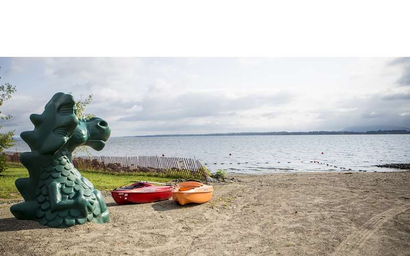 a large dragon beach toy next to a kayak