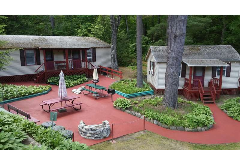 cottages with picnic tables and trees nearby
