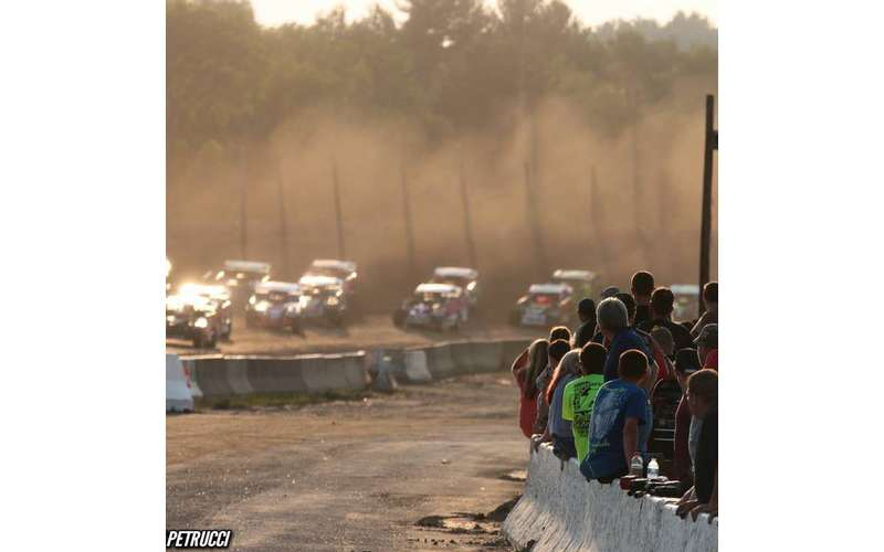 spectators watching as cars speed around a corner