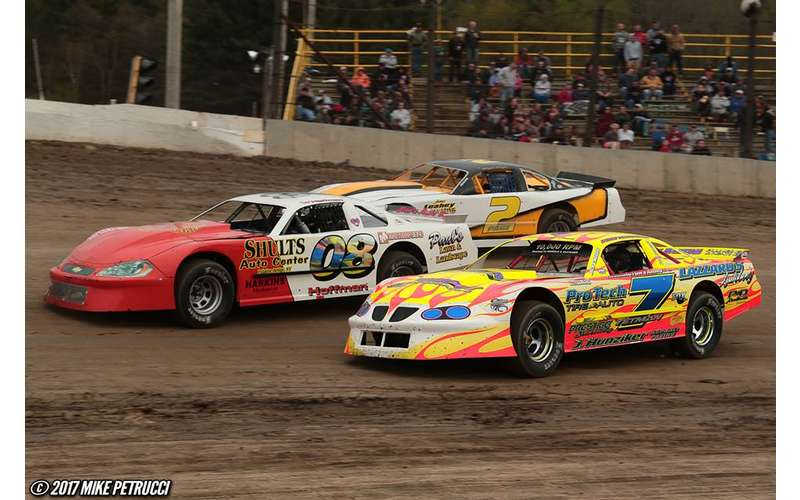 three race cars racing on a dirt track