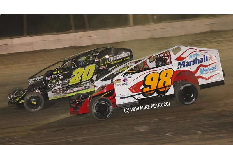 two race cars speeding along on a dirt track