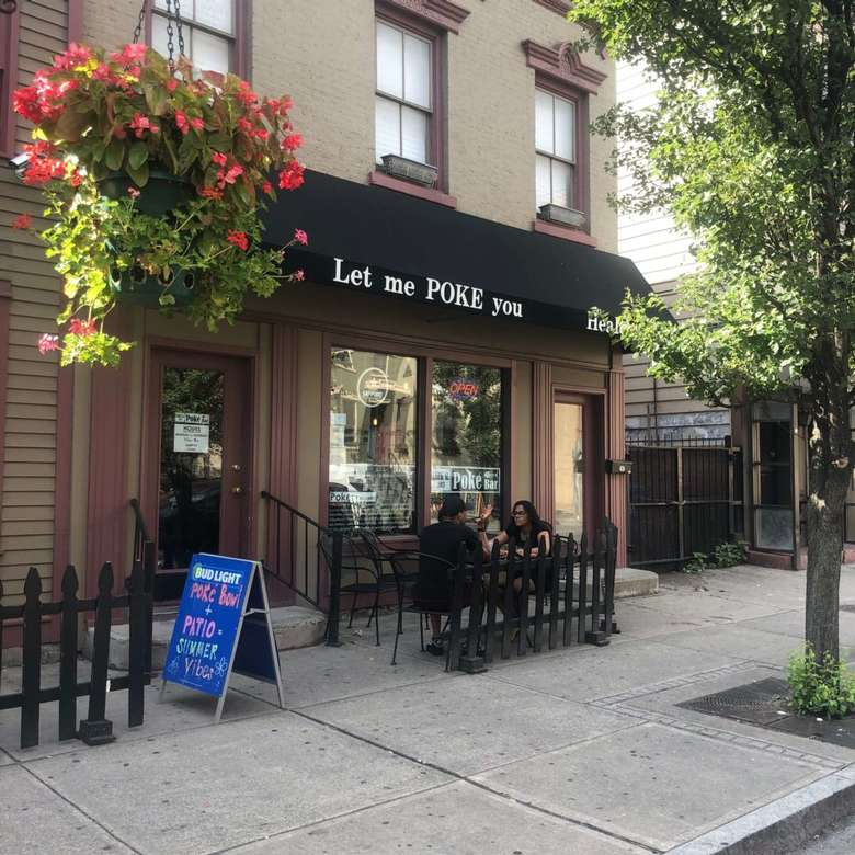 patio seating outside restaurant with roof that says let me POKE you