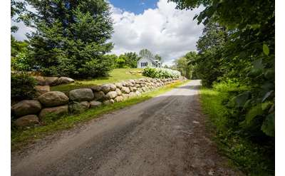 a long dirt road near a stone wall