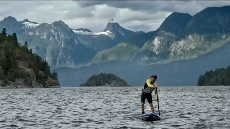 a man stand up paddle boarding with mountains in the background