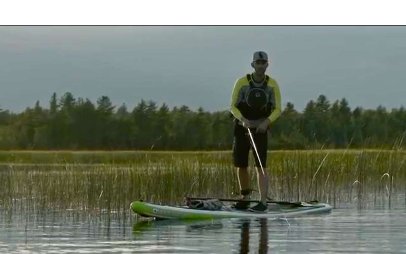 a man fishing on a stand up paddle board