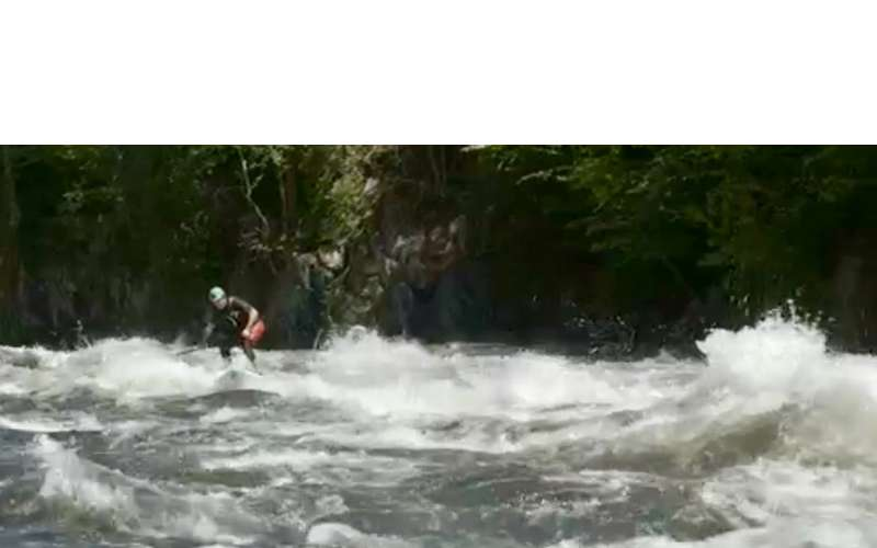 a stand up paddle boarder on rapids