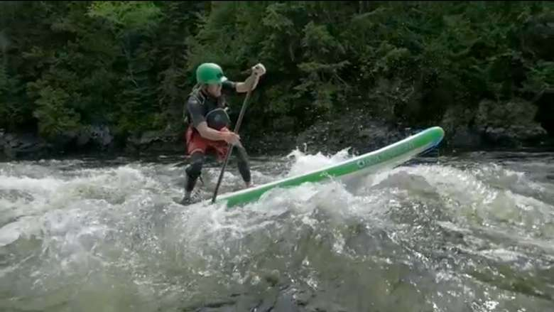 a person stand up paddle boarding on rapids
