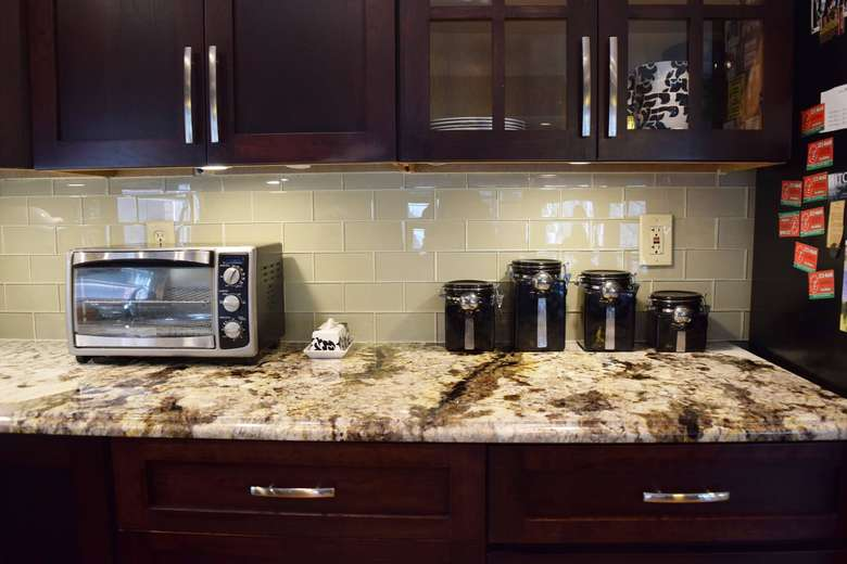 stone kitchen countertop with microwave oven and canisters