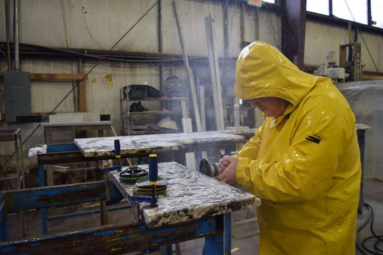 employee in a yellow jacket using power tools