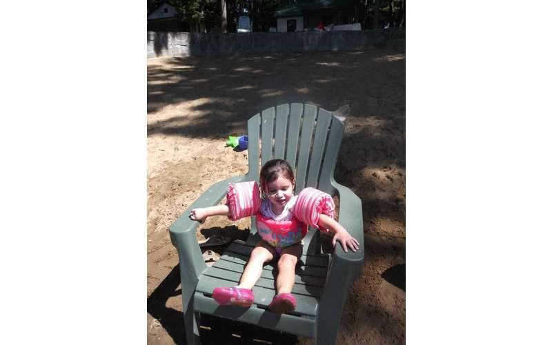 little girl in Adirondack chair.