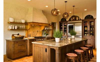 a kitchen with a large island, wooden cabinets, stools, and a wooden floor