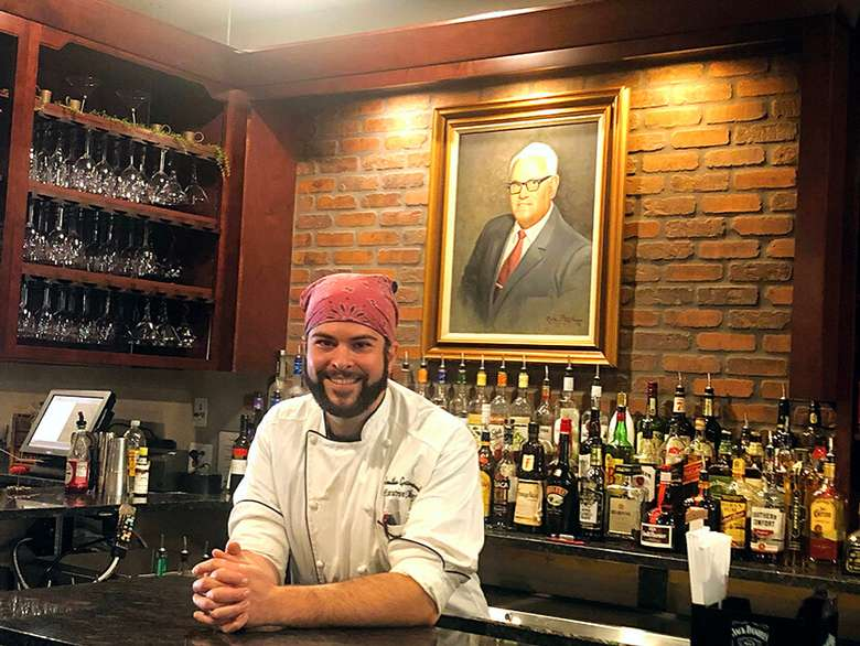man with red bandana leaning on a bar