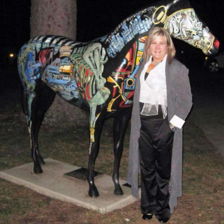a woman standing by a statue of a horse