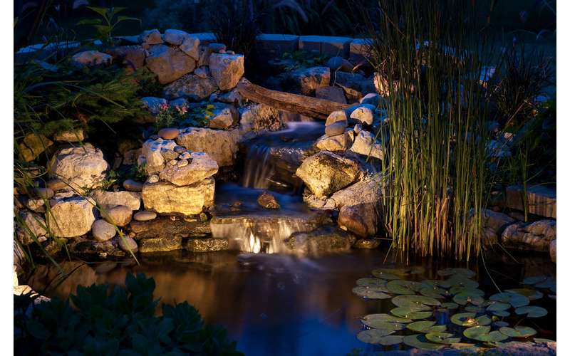 outdoor natural garden waterfall built from stones.