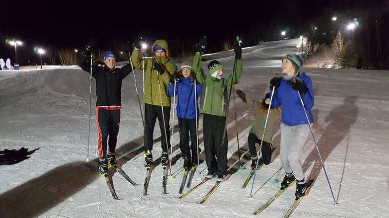 group of six on cross country skis at night