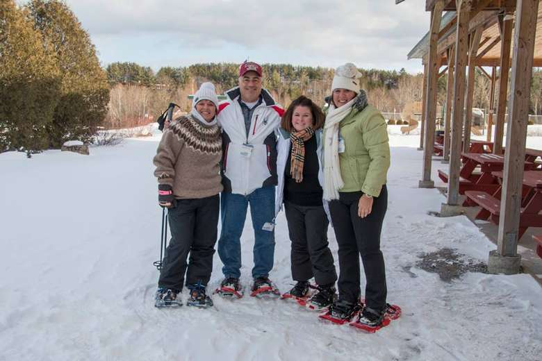 four people wearing snowshoes