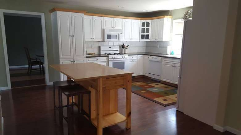 kitchen space with cabinets, counter, oven, and more amenities