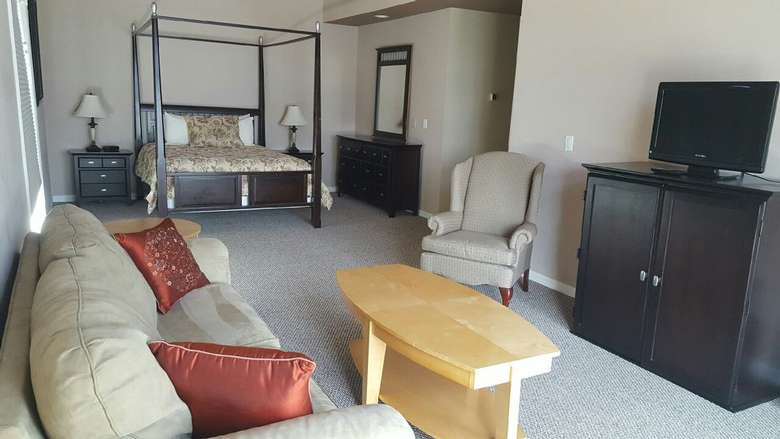 a large master bedroom with a couch, cabinets, tv, and bed