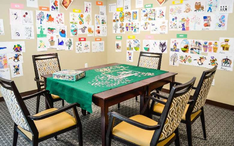 a game room with a puzzle on a table and drawings on the wall