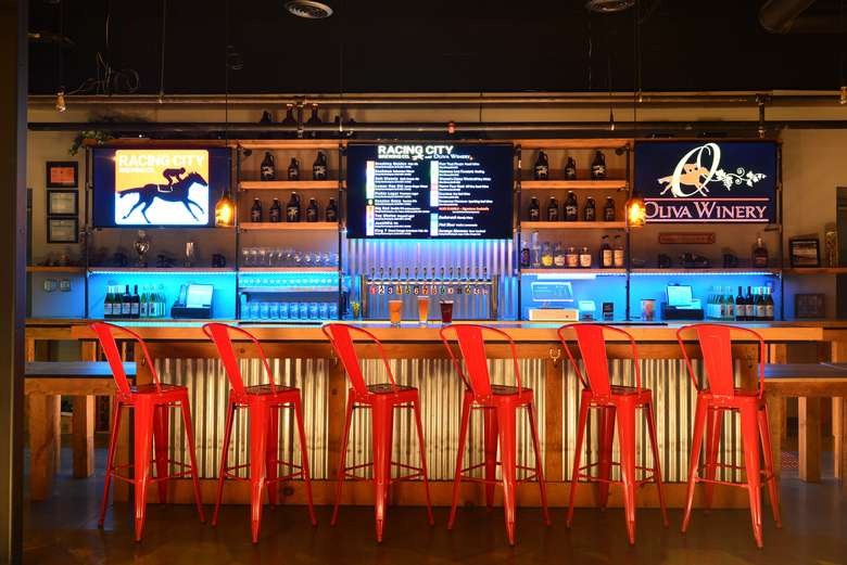 bar with red chairs and glasses, tap, and tvs.