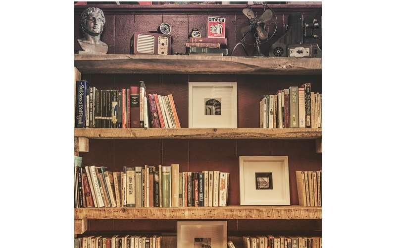 multiple rows of shelves with books and vintage decor
