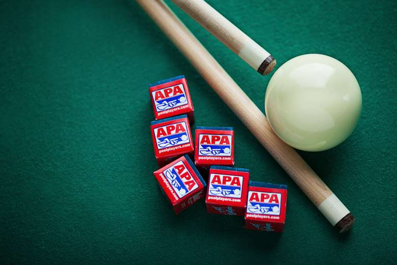 two pool cues, a white ball, and several cubes of chalk on green felt