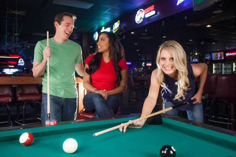 girl shooting pool while a guy and a girl talk in the background