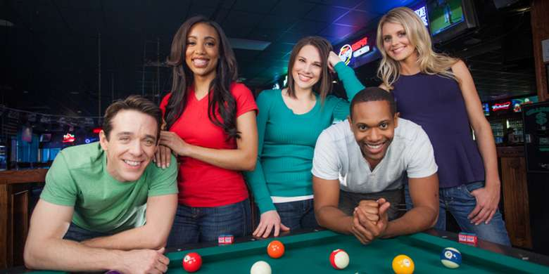 group of friends standing behind a pool table