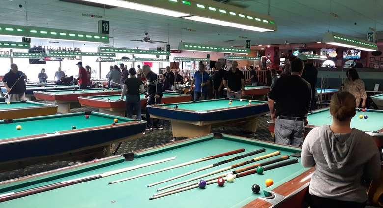 pool tables in a large room with people around them