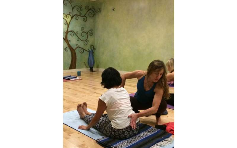 a woman helping another woman practice yoga
