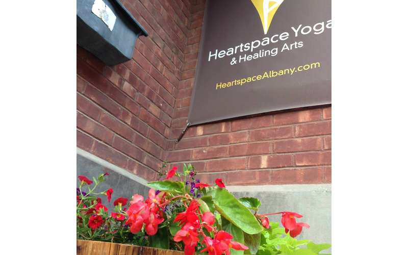 Heartspace Yoga sign on the outside of a building with a plant