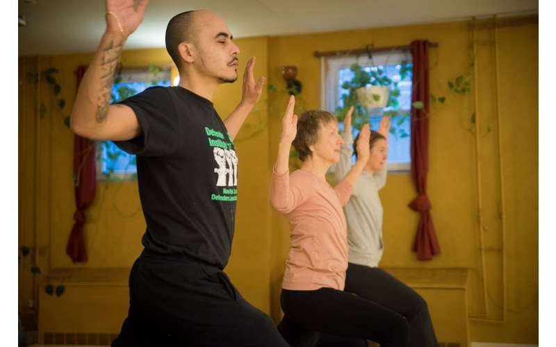 man and two women doing yoga