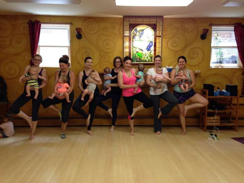 a group of women doing yoga with their babies
