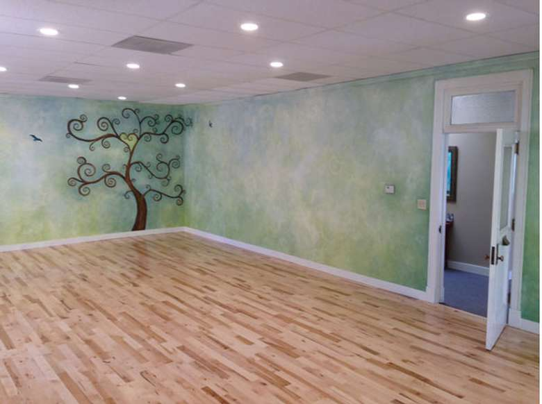 an empty yoga studio with a tree decoration on the wall
