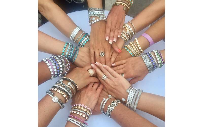 a bunch of women's hands coming together with jewelry on them