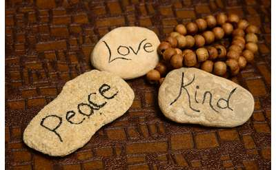 three rocks with the words 'peace,' 'love,' and 'kind.'