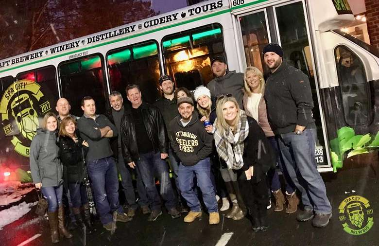 group standing near the spa city brew bus in the evening