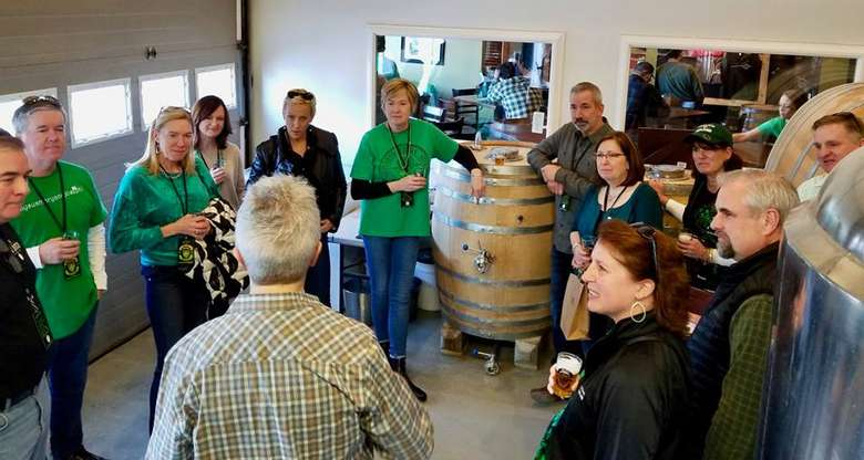 tour group listening to a guide inside a craft beverage room