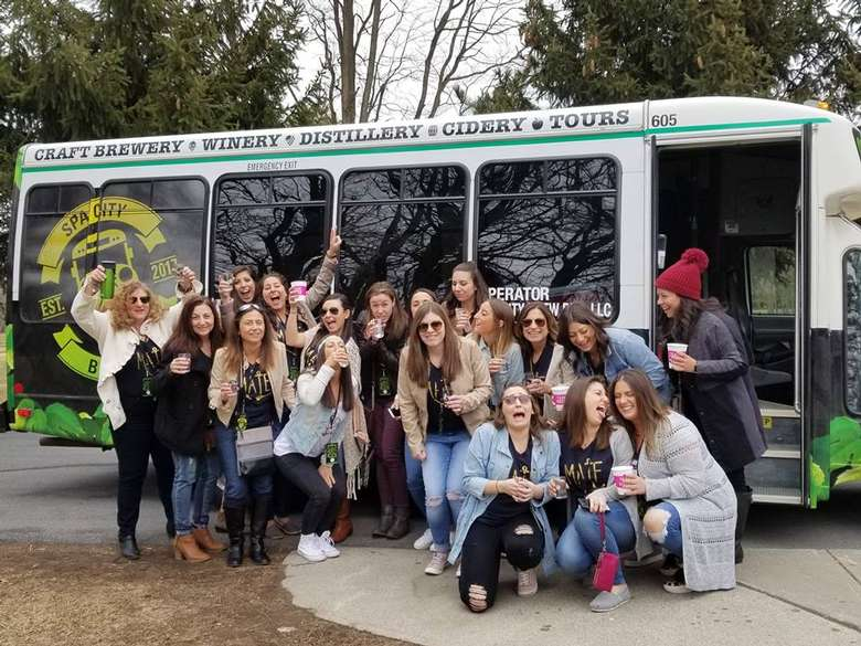 large group of women posing in front of the spa city brew bus
