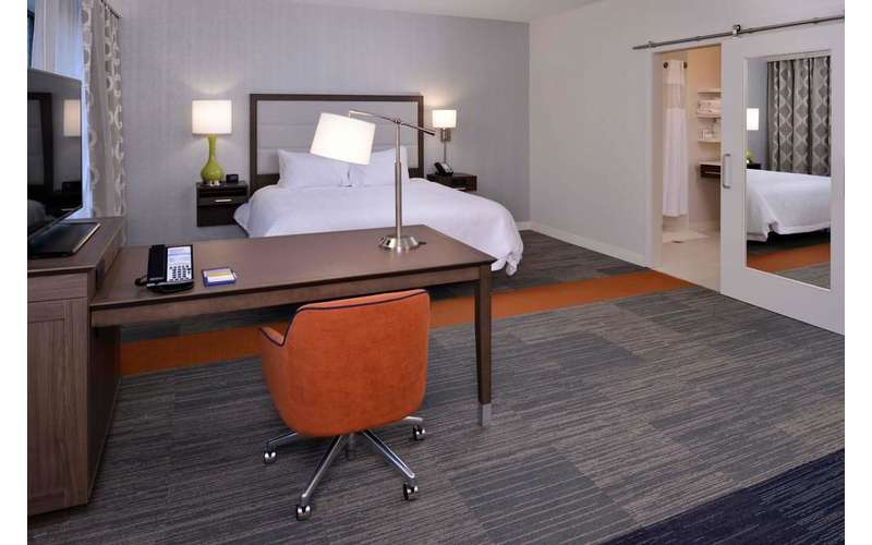 a desk inside a hotel guest room with a bed