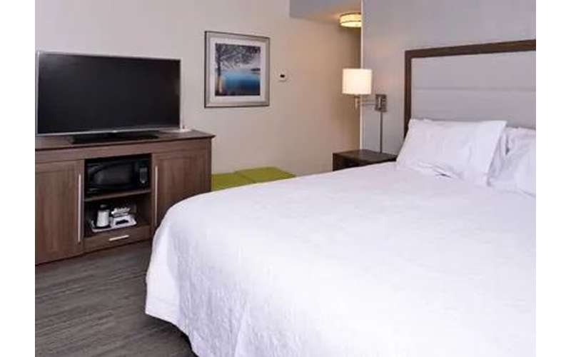 a hotel guest room with a bed and TV
